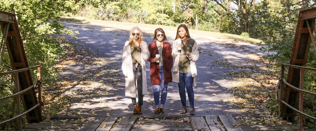 Online women's clothing store. Three girls in trendy sweaters.