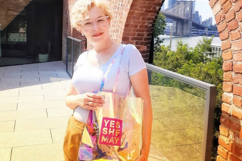 woman outside wearing clear tote bag