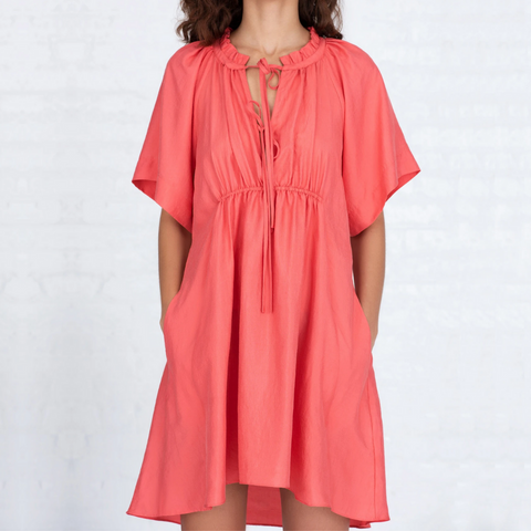 woman wearing salmon/pink colored silk dress with short sleeves, empire waist, tie detail at neckline. Dress hits slightly above the knee