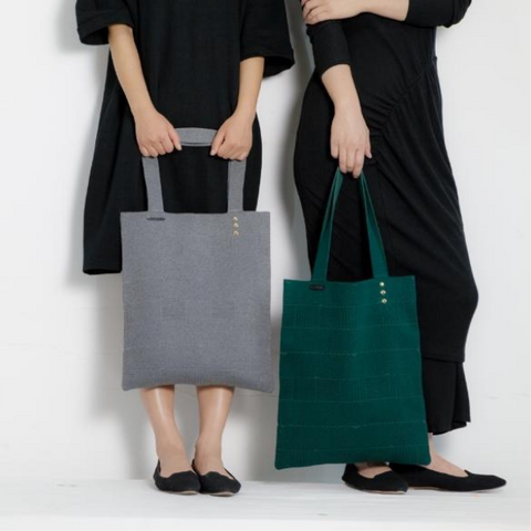 Photo of lower half of two women holding shopping bags