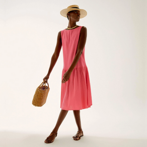 woman wearing a sleeveless coral pink midi dress and a sun hat and bag