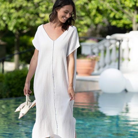 woman outdoors by pool wearing a white v-neck, loose-fit, kaftan dress