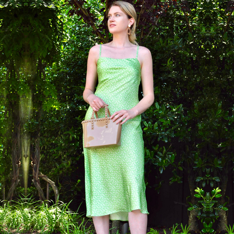woman outdoors wearing thin strap silk midi slip dress that's light green with small white floral pattern