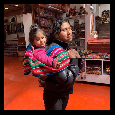 Peruvian woman carries her baby on her back indoors