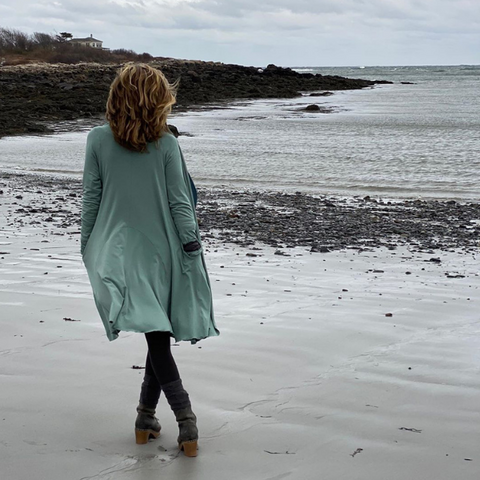 woman wearing long cardigan walking along beach