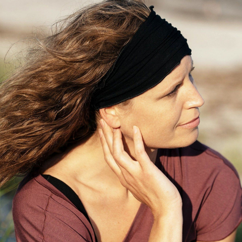 woman outdoors with hand resting on her face