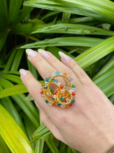 woman's hand outdoors wearing oversized gold and multi color crystal ring