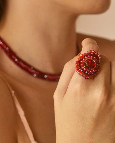 close up of woman wearing red crystal mandala ring and matching red crystal neckace
