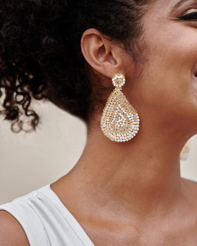 smiling model posing with white and clear crystal tear drop earring