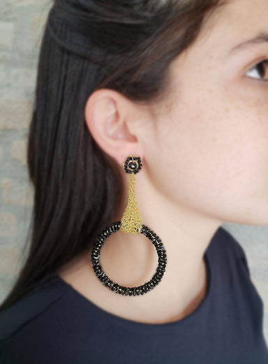 woman posing wearing black crystal beaded earrings with gold chain