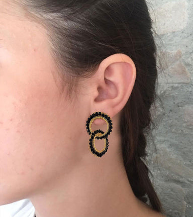 model posing outdoors with gold wire black crystal small double hoop earring