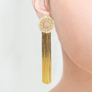 closeup of model wearing duster earring with crystal circle base and long fringe