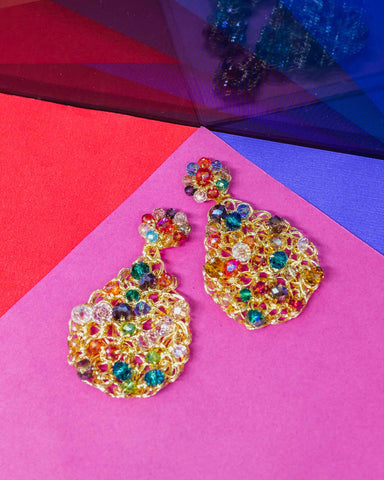 multi color crystal tear drop earrings laying flat on colorful surface