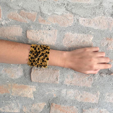 arm against wall wearing a gold thick bracelet with black crystals throughout