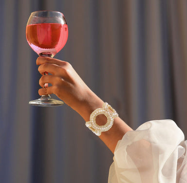woman's arm holding glass of wine in the air wearing circle crystal bracelet