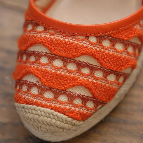Close detail of orange woven detail on closed toe wedge sandal shoe