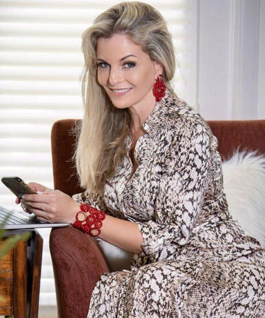 model posing wearing animal print dress and red earrings along with matching red bracelet