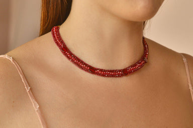 model posing with red crystal necklace