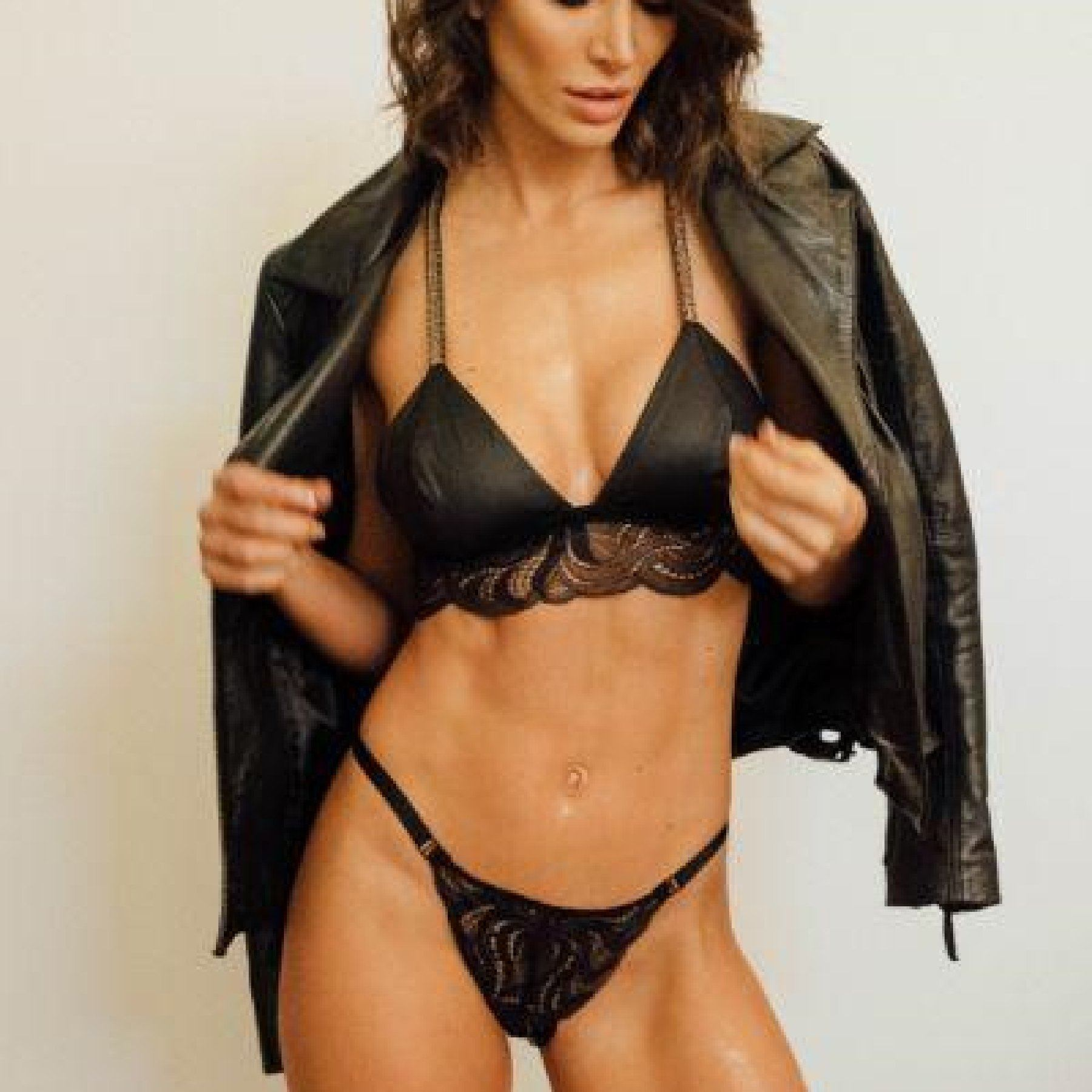 woman wearing black lace bralette and panty with leather jacket