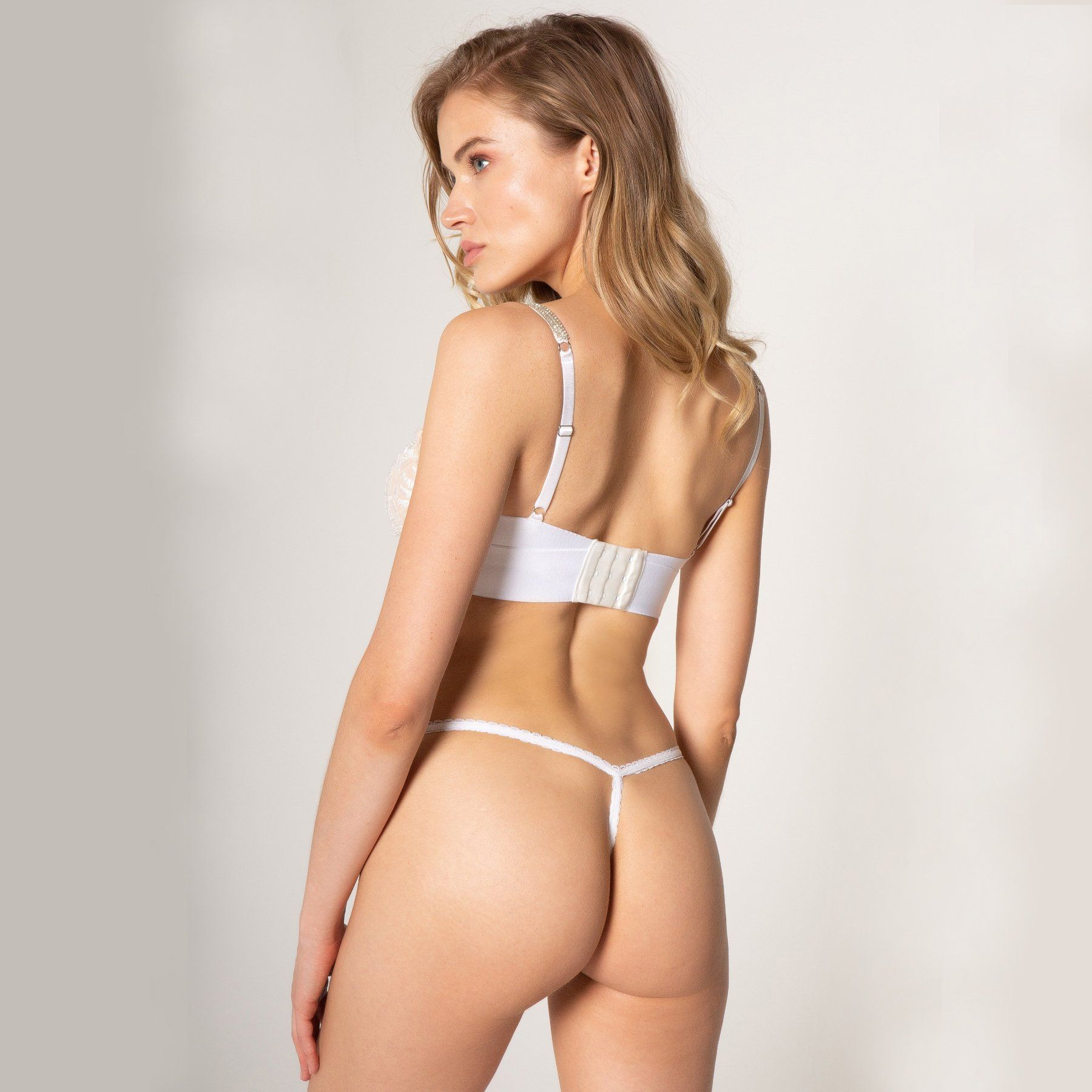 rear view of woman wearing white lace bra and thong