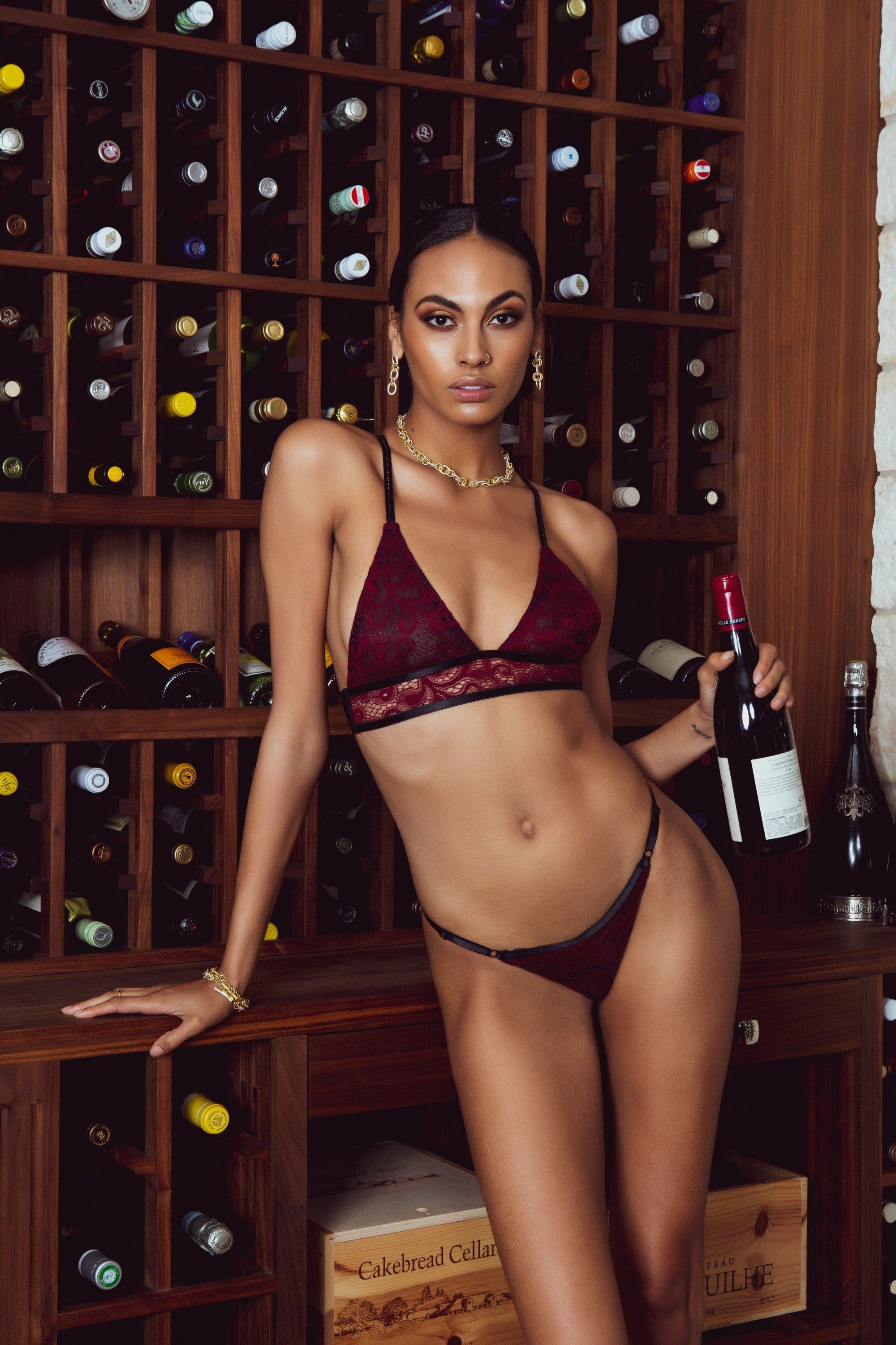 woman wearing red/black lace bra and panty holding bottle of wine in front of wine rack