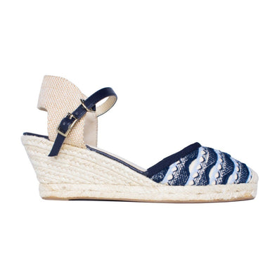Close side view of knit wedge sandal with buckle and navy cotton pattern