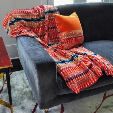 Throw blanket with red pattern on a gray sofa