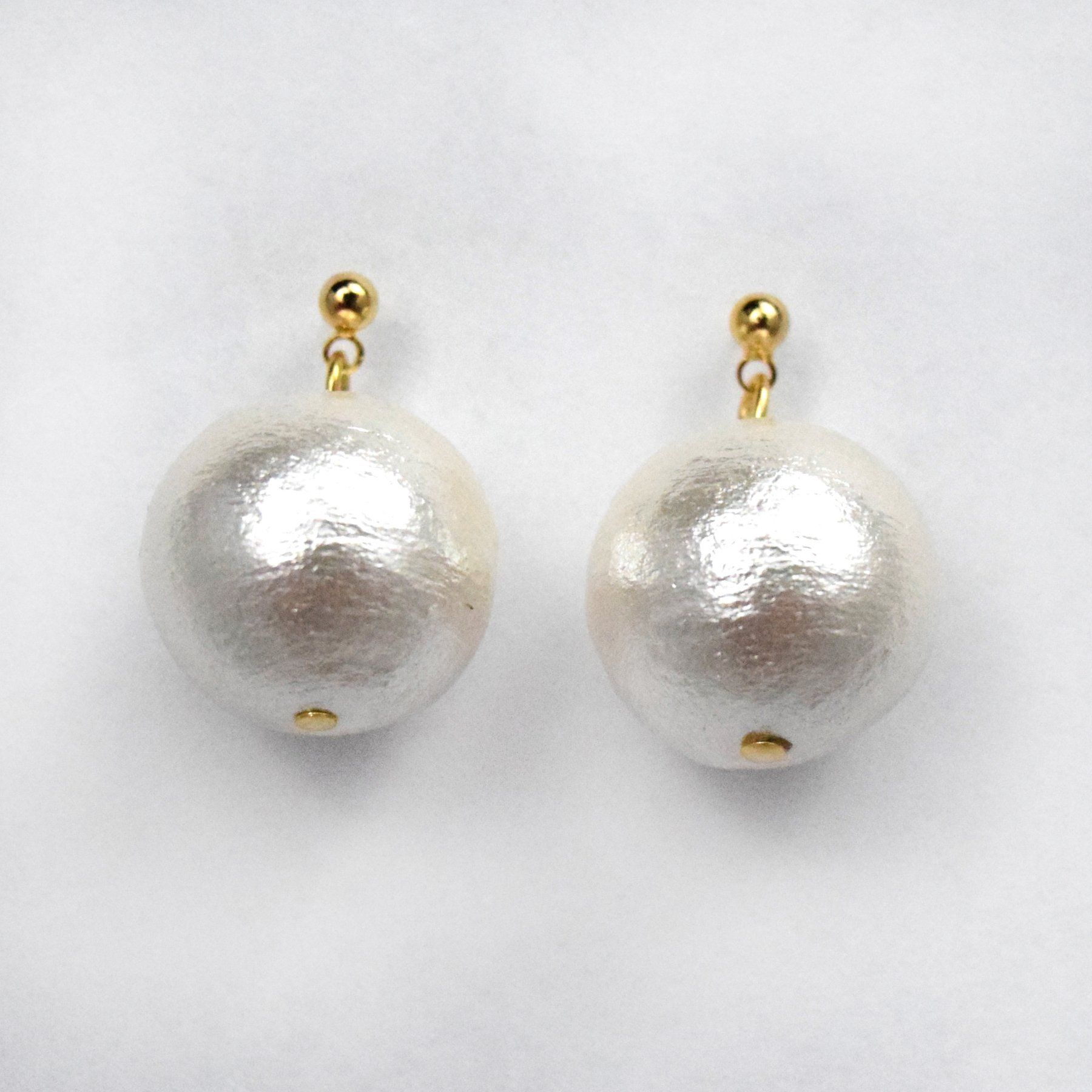 closeup of shiny oversized pearl earrings. Gold studs and short links with pearl.