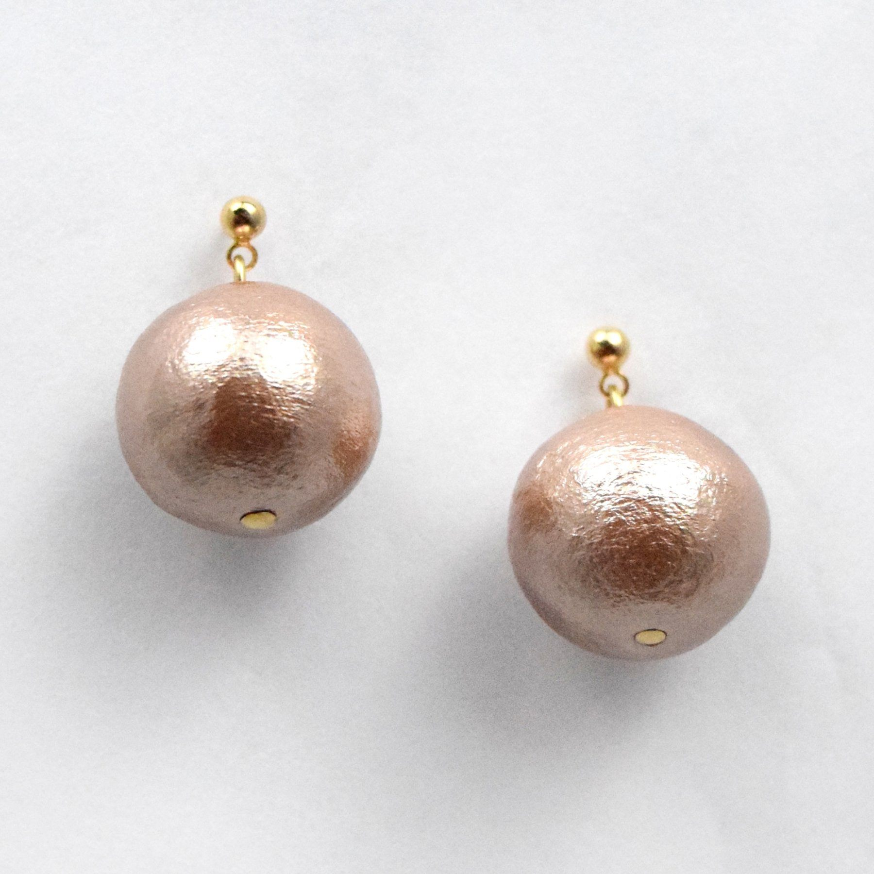 Close detail of pearl drop earrings in bronzed gold color.
