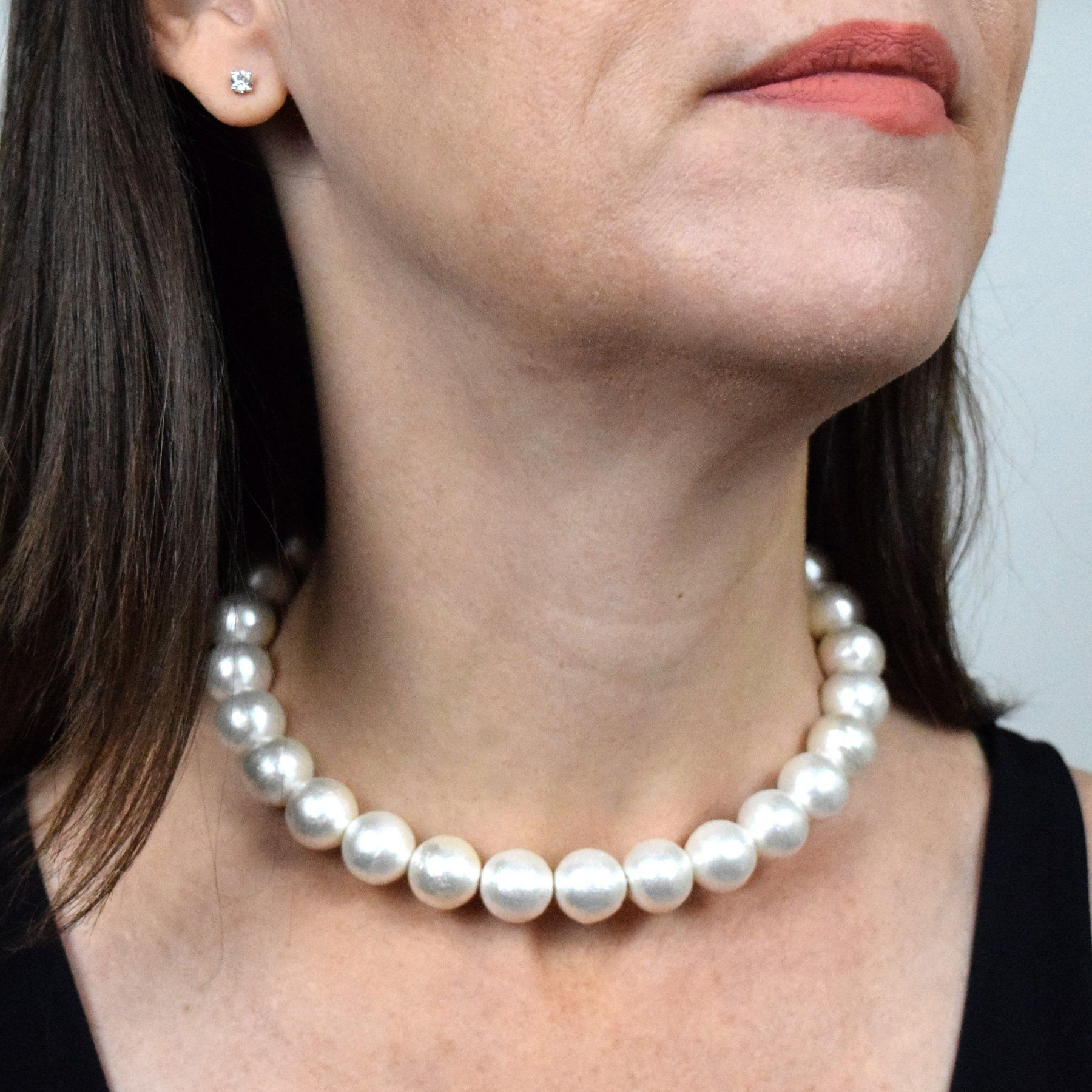 model wearing chunky white pearl choker necklace on neck.