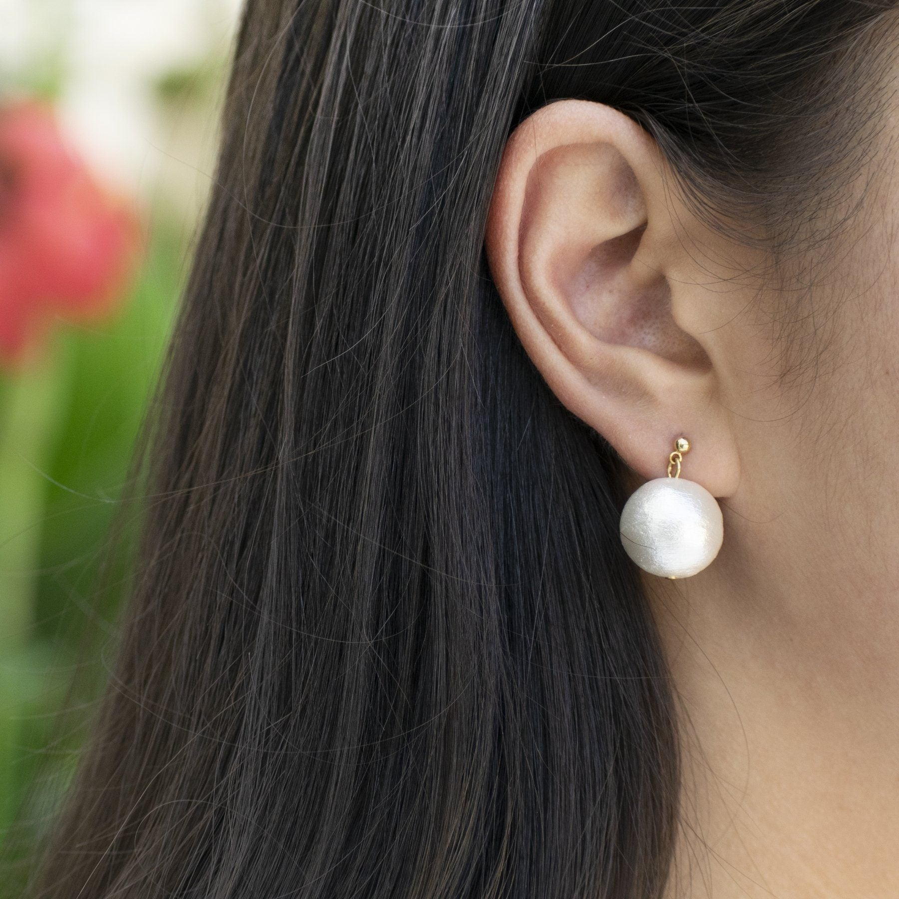 closeup of woman's ear with oversized pearl drop earring