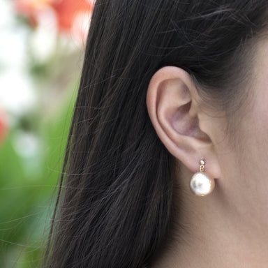closeup of woman's ear with oversized pearl drop earring in gold color.