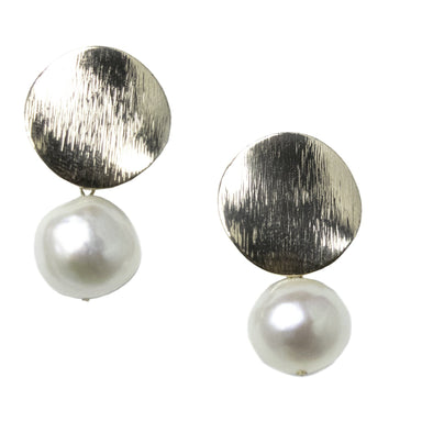 set of earrings closeup. Textured gold disc at  base and drop with a single medium sized white pearl pendant.