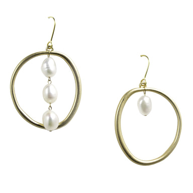 Set of earrings on white background. Both earrings are gold circle shapes with pearls dangling on inner gold circles. One earring has pearl strand of 3, and the other has a single pearl drop.