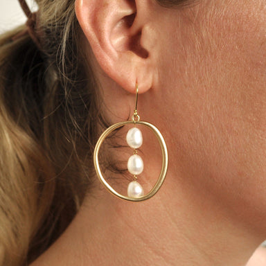 closeup of woman's ear with gold earring featuring gold hook with large gold circle and three strands of white pearls inside the circle.