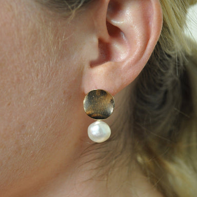 closeup of woman's ear with earring featuring a medium sized gold disc and drop pearl underneath.