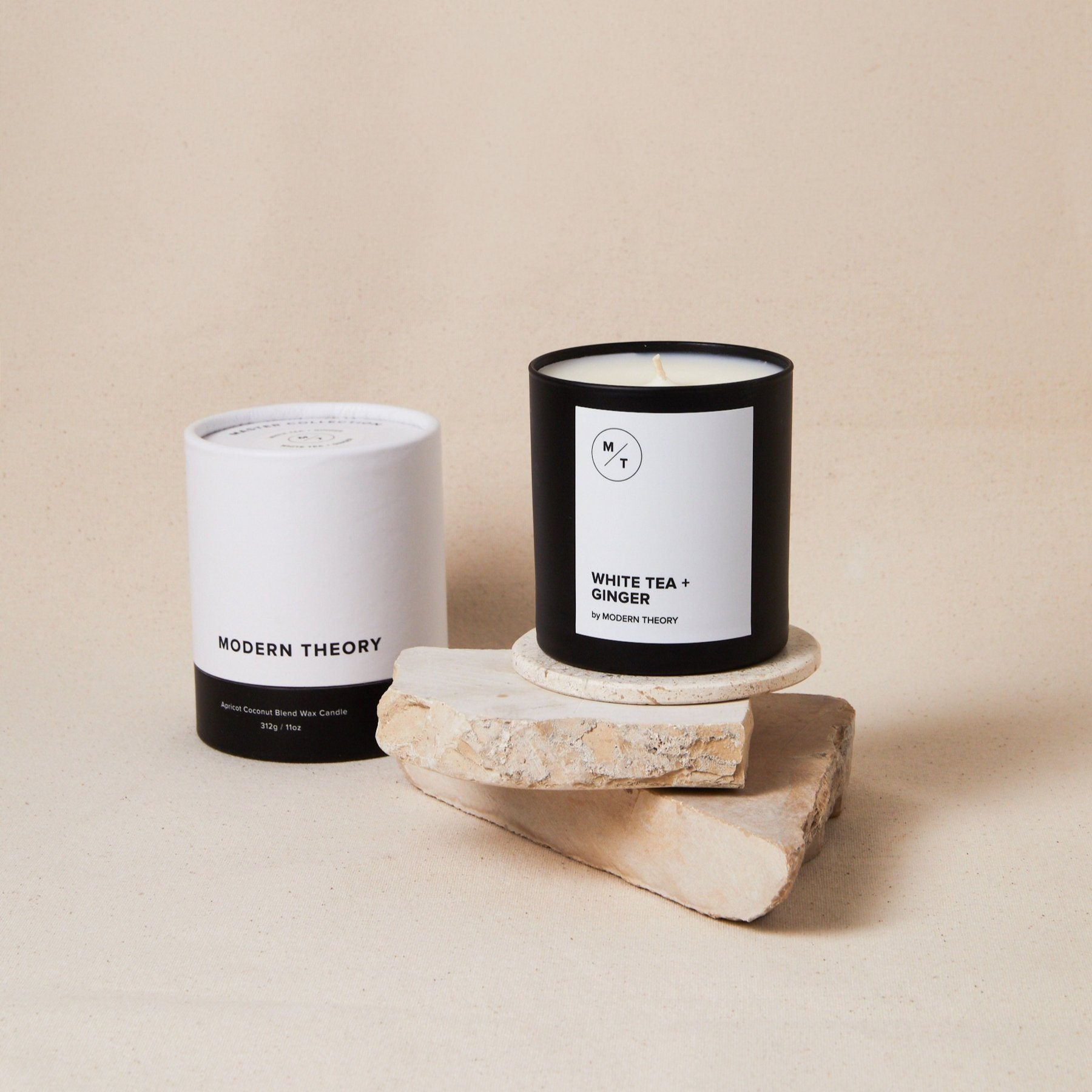 white candle in black glass jar with text, next to its white and black matching decorative box