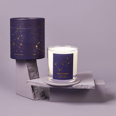 white candle in clear glass jar with purple label and astrology design that reads Sagittarius