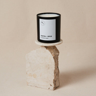 white candle in black glass jar with label that reads: Santal + Spice