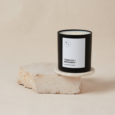 "white candle in black glass jar labeled ""tobacco and bergamot"""