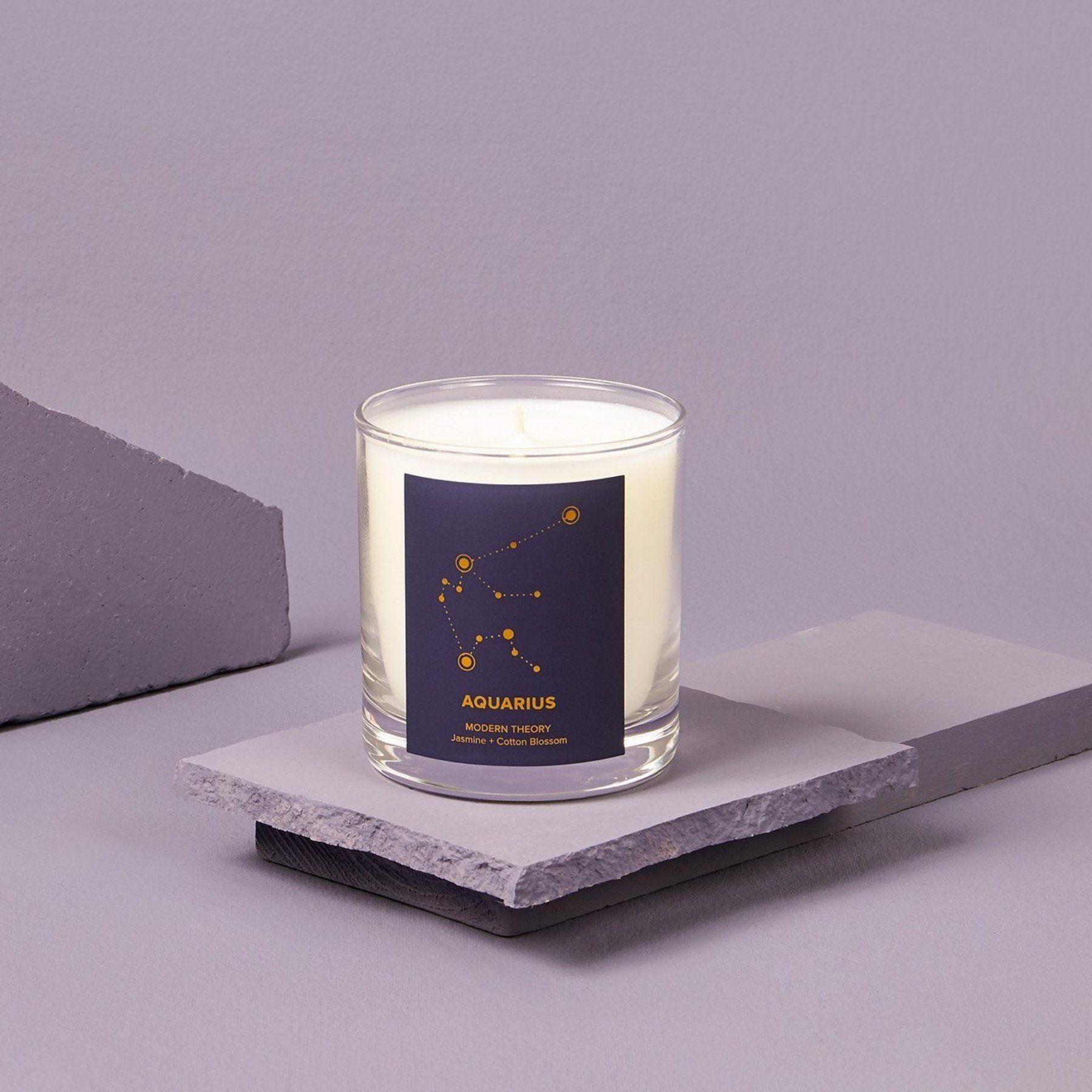 single white candle in glass jar with Aquarius written on the navy blue label.