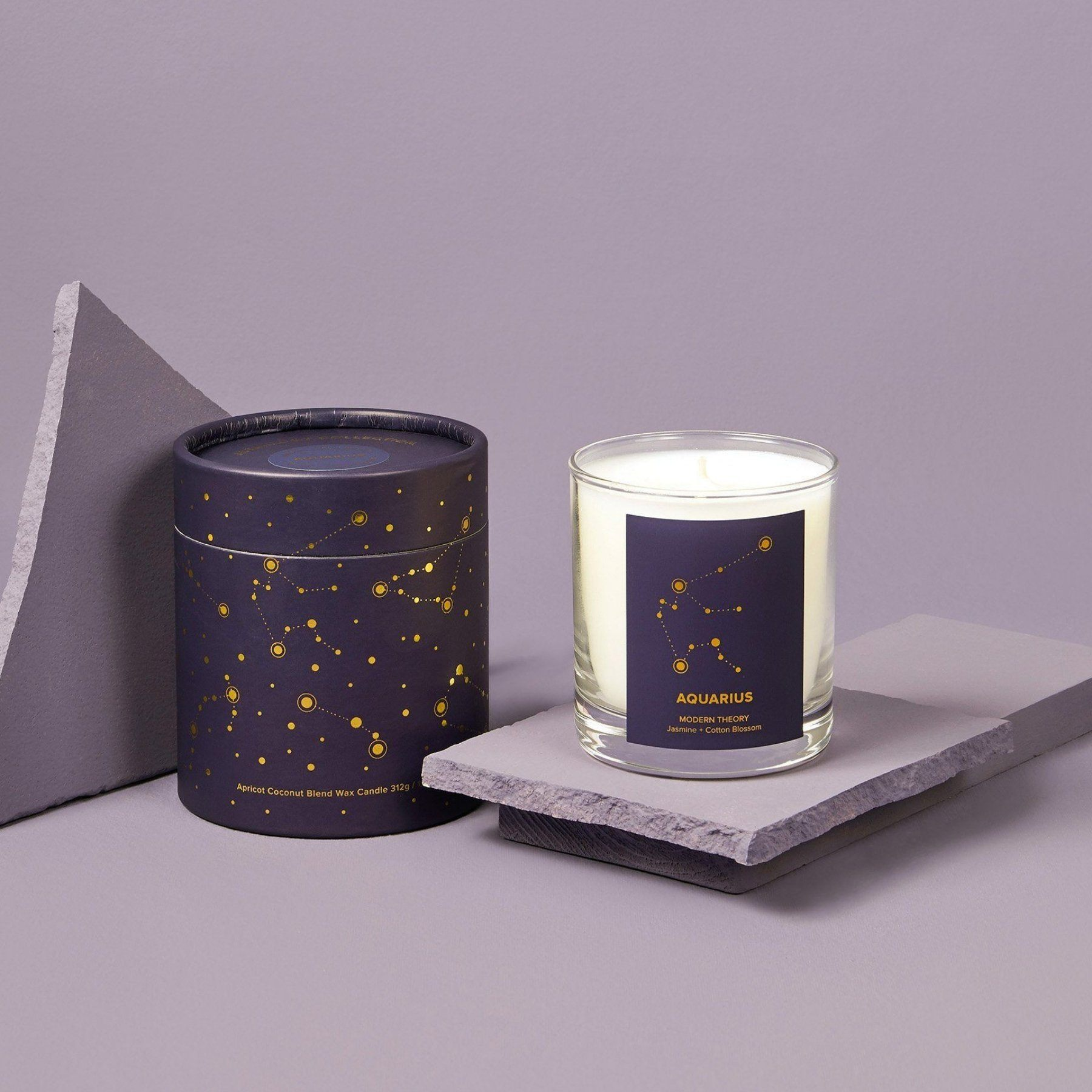 white candle in glass jar with navy label that reads aquarius. Comes with decorative navy box with astrology pattern