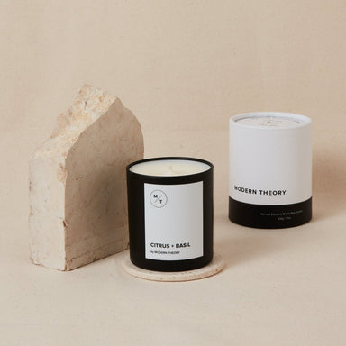 white candle in black glass jar with Citrus and Basil text, next to its white and black matching decorative box