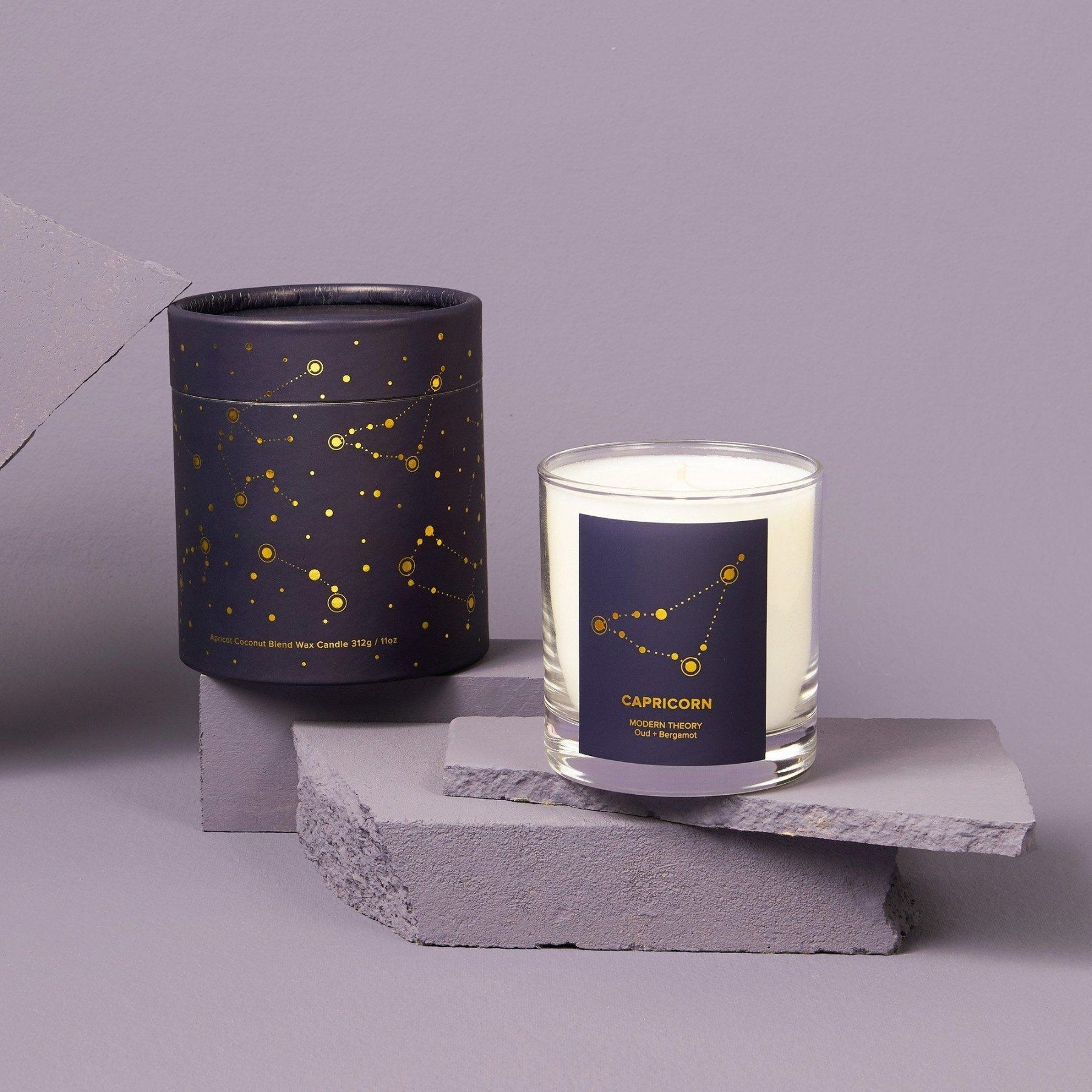 white candle in glass jar with capricorn label next to matching navy decorative box with astrology pattern