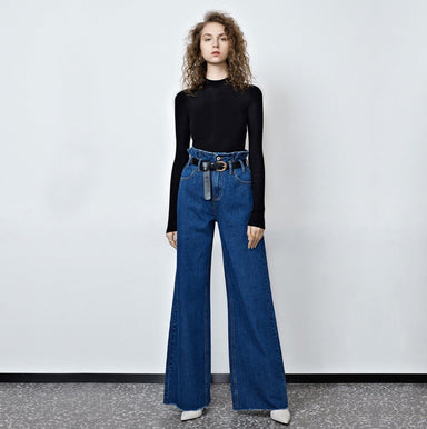 model standing against white background wearing a black long sleeve top and high waist dark blue wide leg jeans with paper bag waist