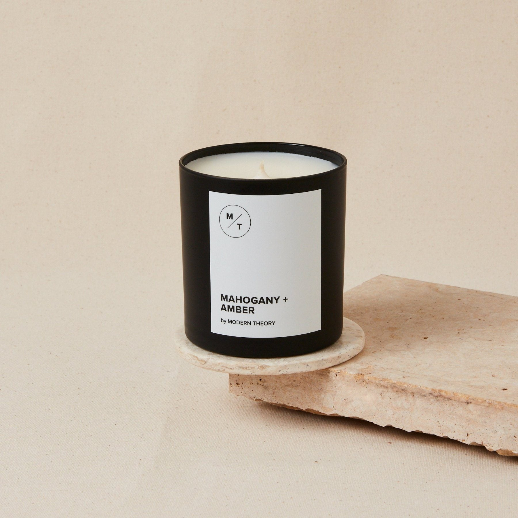 white candle in black glass jar with white label that reads mahogany + amber