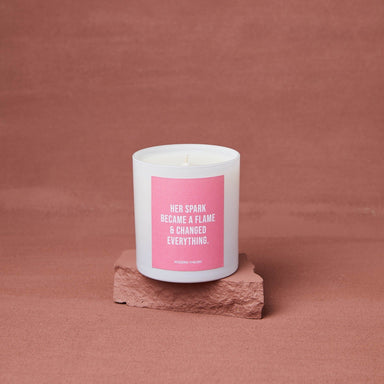 "single white candle in frosted white glass jar with pink label that reads ""her spark became a flame and changed everything"""