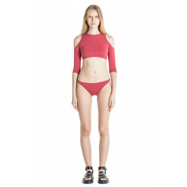 model wearing red color two piece with crop top and bikini bottom