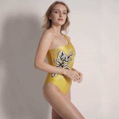 model indoors turning to the side wearing one piece one shoulder gold swimsuit with large flower graphic on side of suit