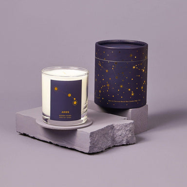 White candle in clear glass jar with navy label that reads Aries. Next to the matching navy gift box with gold astrology design